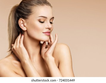Sensual young woman enjoying her fresh clean skin. Portrait of beautiful woman of european appearance on beige background. Skin care and beauty concept