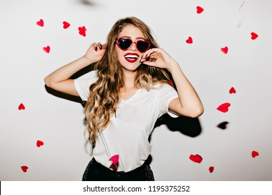 Sensual young woman in funny glasses expressing energy while dancing under confetti. Laughing long-haired girl enjoying valentine's day.