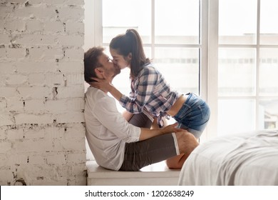 Sensual young woman kissing loving man sitting on windowsill at home, lovers enjoying passionate foreplay in bedroom, wife and husband having romantic date, sweet prelude hugging before love making