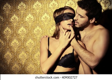 Sensual young woman with lace ribbon on her eyes and a handsome man kissing and playing in love games.