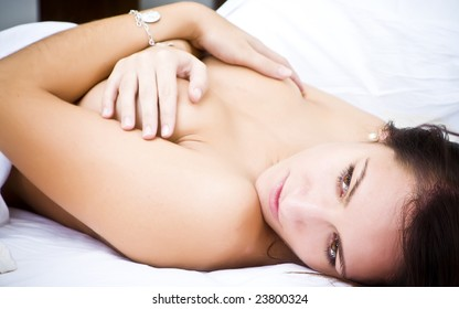 Sensual young woman laying nude in white sheet.