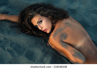 sensual young woman lie in sand at sunset