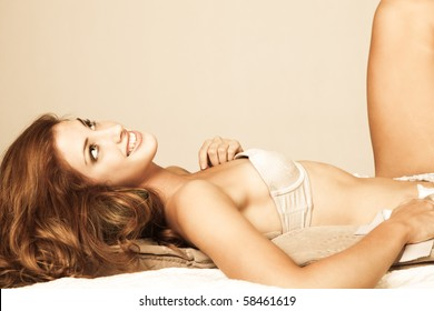Sensual young woman with long red hair lies atop pillows. She is wearing a strapless bra and smiling upwards. Horizontal shot.