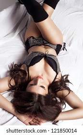 Sensual young woman lying on the bed, studio shot