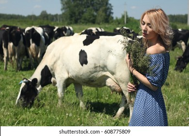 Sensual young woman milkmaid in summer pasture.