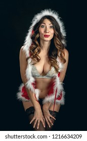 sensual young woman in miss santa costume on black background show her breasts, looking at camera
