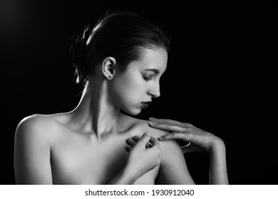 sensual young woman on black background with copy space, monochrome