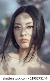 Sensual young woman portrait at blossoming tree in the garden. Beauty of woman and nature consept. Close-up face of beautiful asian model posing and looking at camera.