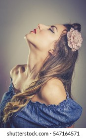 Sensual young woman in vintage fashion wearing an off the shoulder top and flower in her long hair standing with her head tilted back and eyes closed, toned portrait