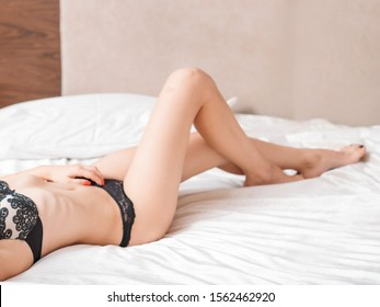 Sensuality and allure. Perfect slim female body in black lace lingerie on bed.