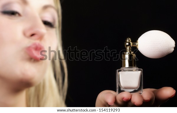 Sensuality concept. Portrait beautiful woman  kiss on lips with perfume bottle on black background