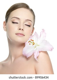 Sensuality girl with lily on the shoulder with healthy skin - vertical