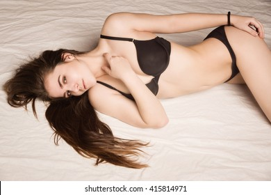 Sensuality young woman with perfect body lying in bed. Boudoir type shooting.
