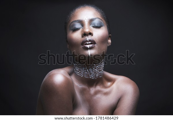 Sensuous young woman with painted face over black background