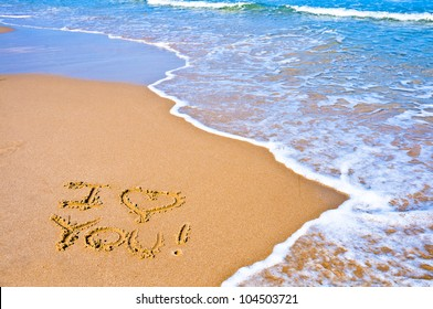 "sentence ""I love you"" written on the sand of a beach"