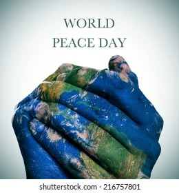 the sentence world peace day  and a world map in man hands forming a globe (Earth map furnished by NASA)