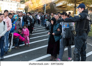 SENTILJ, SLOVENIA - 15 OCTOBER 2015: Syrian refugees on the road from the accommodation camp escorted by police to the Slovenian Austrian border