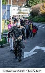 SENTILJ, SLOVENIA - 15 OCTOBER 2015: Syrian refugees on the road from the accommodation camp escorted by army to the Slovenian Austrian border