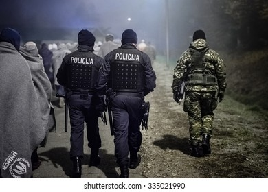 SENTILJ, SLOVENIA - 3 NOVEMBER 2015: Syrian refugees on the road from the train escorted by police and army to the camp at the Slovenian - Austrian border.