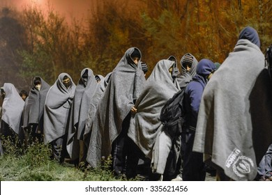 SENTILJ, SLOVENIA - 3 NOVEMBER 2015: Syrian refugees on the road from the train to the camp at the Slovenian - Austrian border. Refugees are wrapped in a blanket because it is cold night outside.