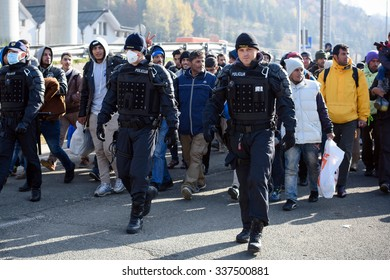 SENTILJ, SLOVENIA - 4 NOVEMBER 2015: Syrian refugees on the road from the train escorted by police to the camp at the Slovenian - Austrian border.