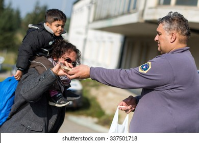 SENTILJ, SLOVENIA - 8 NOVEMBER 2015: Slovenian police officer helps and gives food to Syrian refugees