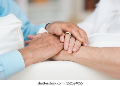 Sentimental conceptual image of love, commitment and support between two elderly people as they tenderly hold hands, close up view