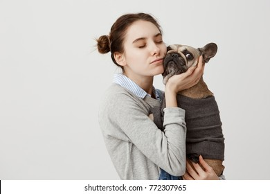 Sentimental woman pressing her cheek to french bulldog being isolated over white background. Female pet owner expressing care and love hugging her pedigree dog while walking in park. Copy space