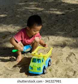 SENTOSA ISLAND, SINGAPORE - NOV 15, 2015: An unidentified Asian boy is scooping sand to fill up his plastic toy truck at Siloso beach. Active outdoor activity for kid concept. Summer background