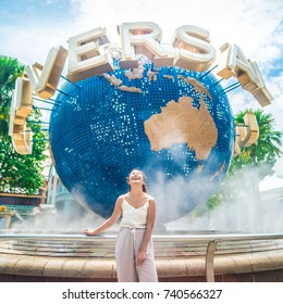 Sentosa, Singapore, October 13, 2017: Asian tourist taking photo with The Universal Globe landmark of Universal Studios Singapore located within Resorts World Sentosa on Sentosa Island, Singapore.