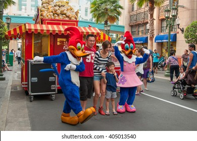 Sentosa Universal Studios, Singapore - 1 March, 2014 : A happy family took photo with Woody Woodpecker and Winnie Woodpecker,