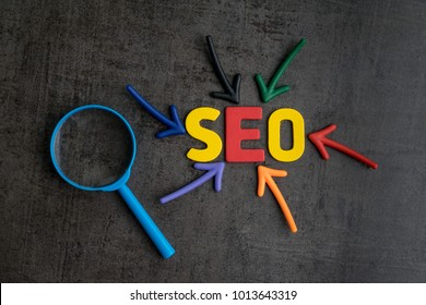 SEO, Search Engine Optimization ranking concept, magnifying glass with arrows pointing to alphabets abbreviation SEO at the center of cement wall chalkboard, the idea of promote traffic to website.