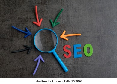 SEO, Search Engine Optimization ranking concept, arrows pointing to magnifying glass with alphabets abbreviation SEO at the center of cement wall chalkboard, the idea of promote traffic to website.