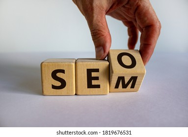 SEO vs SEM. Male hand turns a cube and changes the expression 'SEO' to 'SEM', vice versa. Concept for SEO and SEM or Search Engine Optimization and Search Engine Matketing. Beautiful white background