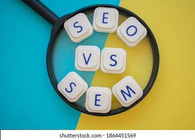 """""""SEO vs SEM"""" words over a magnifying glass, on a blue and yellow background. Search engines concepts as Search engine optimization and search engine marketing"""