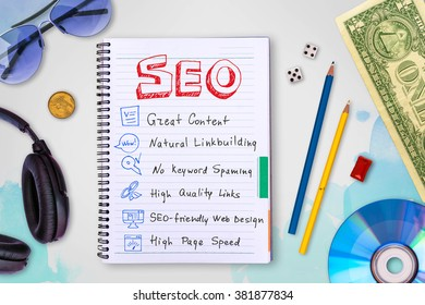 Seo and web development tips collection in a notebook, creative idea concept background with watercolor splashes, cd disk, headphones, dollar, dice photo collage, top view, flat lie