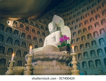 SEORAKSAN, SOUTH KOREA - CIRCA DECEMBER 2015: Buddha statue in a cave tempe in Seoraksan national park. Wall with many carved Buddha niches in the background. South Korea, December 2015