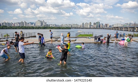 SEOUL - AUGUST 10, 2019 : Visitors and general public cooling off at outdoor pool along Hangang River. Heat wave is getting more common during the summer due to climate change.