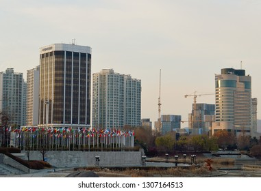 SEOUL, KOREA - 2 DECEMBER 2018: The cityscape behind the competing nations' flags in the Olympic Park in Songpa-gu built for the 1988 Olympic Games