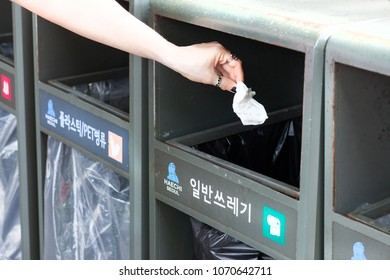 SEOUL, KOREA - APRIL 28, 2015: Woman throwing paper napkin into special trash can