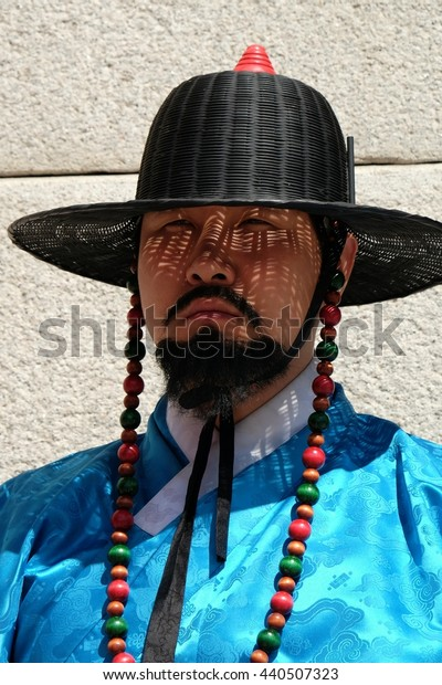 SEOUL, KOREA - APRIL 4, 2016: Close portrait of a Royal Guard standing in front of the main gate to Gyeongbokgung Palace.