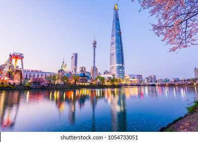 SEOUL, KOREA - APRIL 7, 2016: Lotte World Seokchon Lake park at night and cherry blossom of Spring in Seoul, South Korea on April 7, 2016
