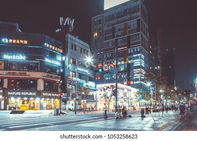 SEOUL, KOREA - AUGUST 12, 2015: Young people walking by a busy main street of Sinchon district at night - Seoul, South Korea