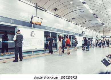 SEOUL, KOREA - AUGUST 12, 2015: Lots of different people standing in the line on a subway platform and patiently waiting for their train to come - Seoul, South Korea