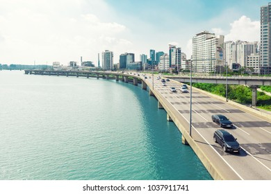 SEOUL, KOREA - AUGUST 14, 2015: Different cars passing highway road along Han river with business and residential area near it - Seoul, South Korea