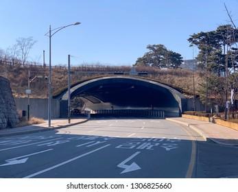 "Seoul, Korea - January 26, 2019: A short tunnel located on Sowol-ro 3 on Namsan Mountain, Seoul, South Korea. The translation on the text: ""Sungnyemun, Huam-dong, City Hall direction""."