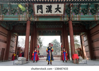 SEOUL, KOREA - MARCH 01: Armed soldiers in period costume guard the entry gate at Deoksugung Palace, a tourist landmark, in Seoul, South Korea on March 01, 2013