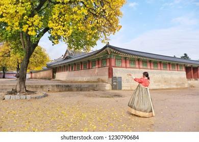 Seoul korea -October 26,2018 : tourist standing under beautiful tree ,wear hanbok dress at Gyeongbokgung Palace.
