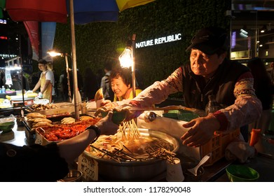 SEOUL, KOREA - OCTOBER 8, 2015 : Myeong-Dong shopping street, Tourists buy street food eaten during a walking and shopping the neighbourhood. It is fashionable to be the most popular. must when travel