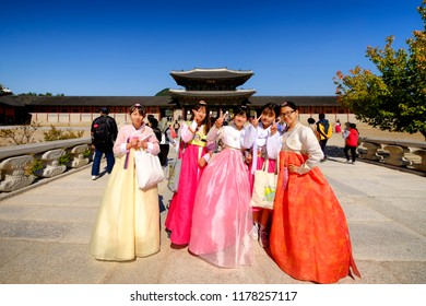 SEOUL, KOREA - OCTOBER 9, 2015 : Gyeongbokgung Palace, Women wearing ็Hanbok traditional ancient dress, walking in the old palace with beautiful architecture. One of Korea's must-see places to visit.
